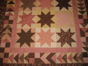 Pink and brown Sawtooth Stars made with fabrics from Henry Glass