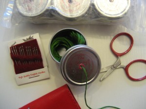 THE STRING THING, along with teeny-tiny airplane approved scissors, and a package of the best embroidery needles EVER!